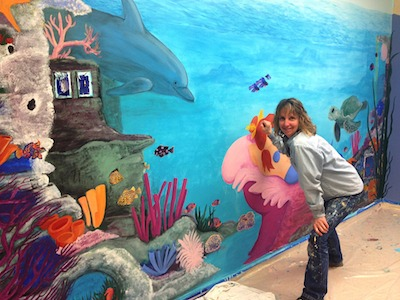 Andrea Lyle puts the finishing touches on a 150-square-foot wall mural at Vibrant Life Enrichment Center, a new day care center for seniors, in Greensboro.